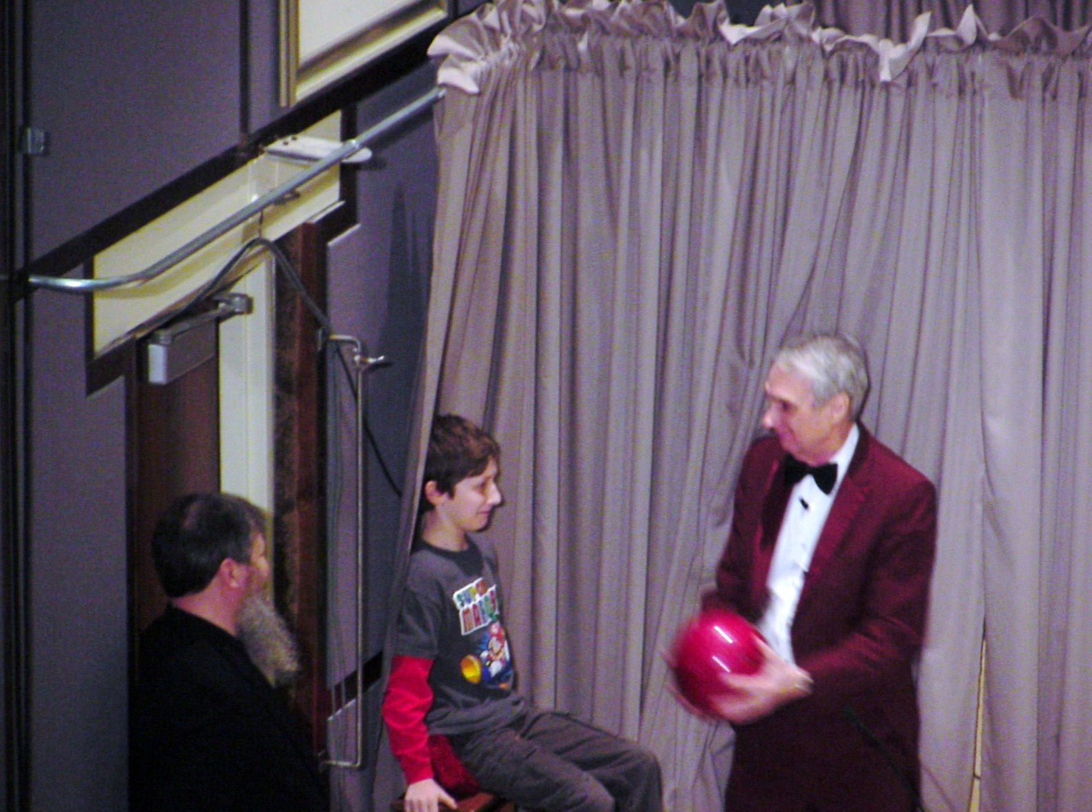 Man shows boy a ball on stage