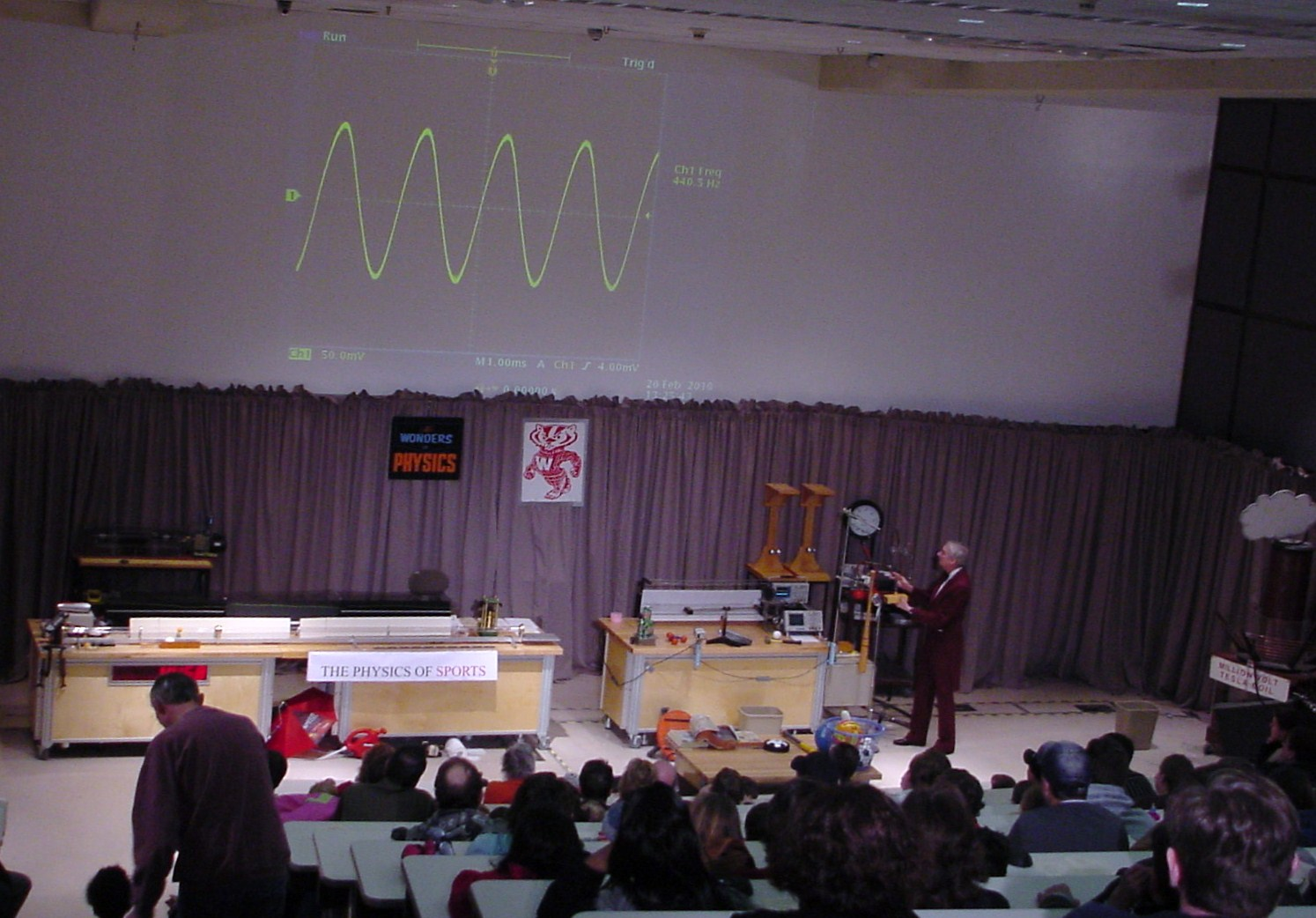 Man on stage presenting sound waves