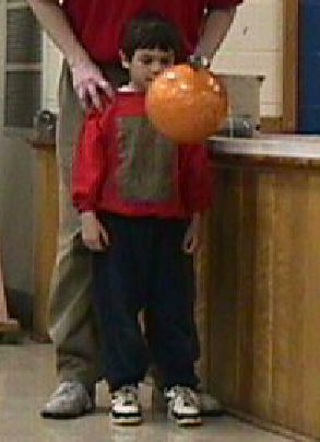 Boy standing in front of bowling ball suspended from the ceiling