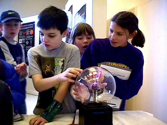 Kids with hands on a plasma ball