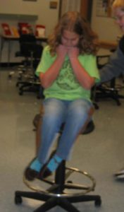 Girl Spinning in chair with arms close to her chest