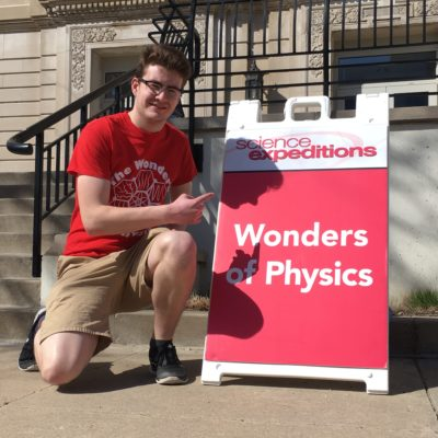 Student crouches in front of sign